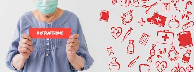 Вид спереди пожилой женщины с медицинской маской, держащей сообщение