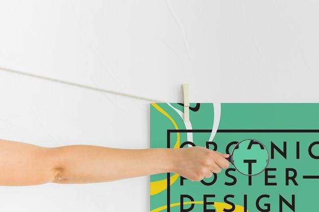 ポスターの上に虫眼鏡を置く腕の正面図