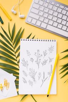 Макет ноутбука сверху и ручка рядом с тропическими листьями