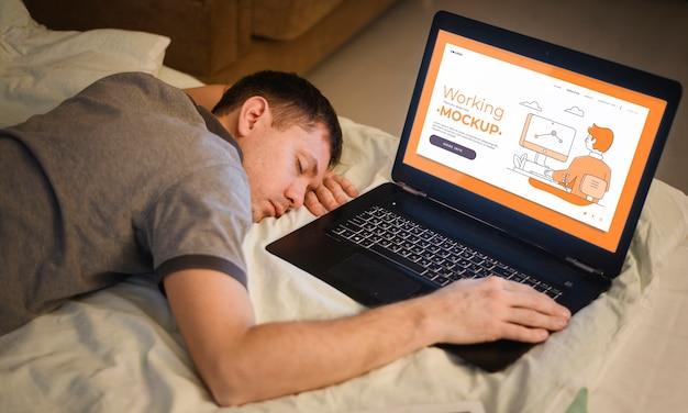 Вид сбоку человек спит в постели во время работы на ноутбуке
