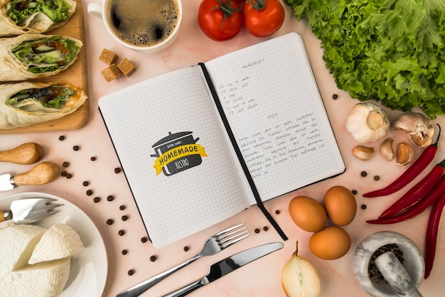 Вид сверху книга рецептов с ингредиентами и сыром