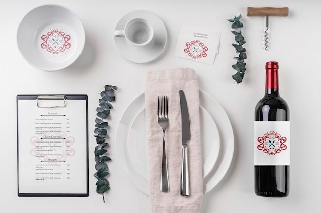 Вид сверху бутылка вина с тарелками и столовыми приборами