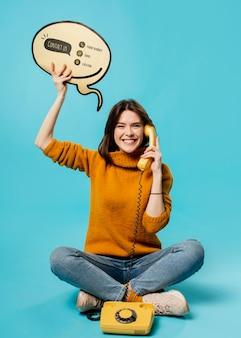 チャットの吹き出しと古い電話のモックアップを持つ女性