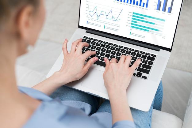 Макро женщина работает на ноутбуке с макетом