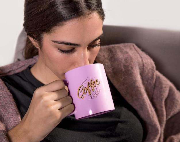 Женщина пьет из розовой кружки