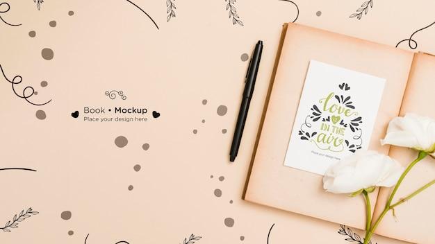 バラとペンで開いた本のフラットレイアウト