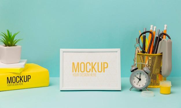 Рамка в окружении карандашей и будильника с макетом