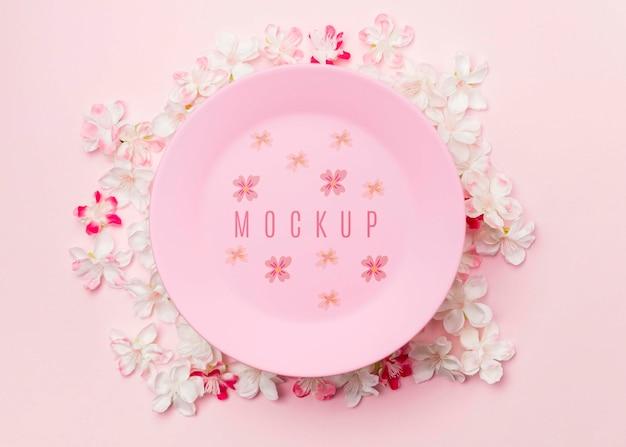 Розовая тарелка макет в окружении цветов жасмина