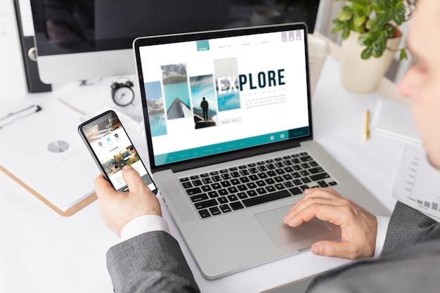 Бизнесмен работает на стол с макет ноутбука и телефона