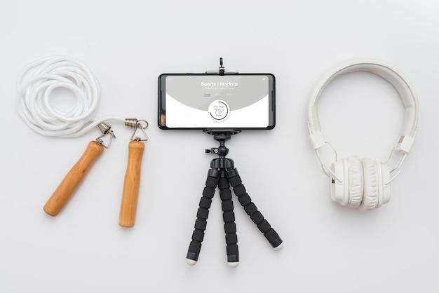 縄跳びの横にある携帯電話とヘッドフォン