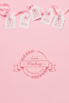 トップビューの誕生日プレゼントタグピンクのリボンのモックアップ