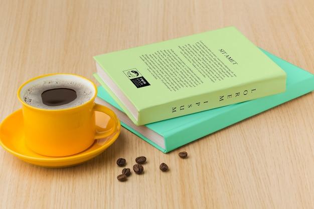 一杯のコーヒーと木製の背景の本カバーの配置