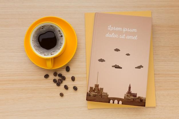 一杯のコーヒーと木製の背景の本カバー品揃え