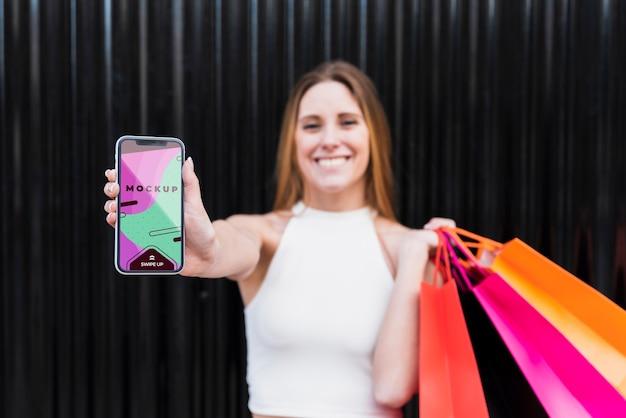 Вид спереди смайлик женщина, держащая телефон