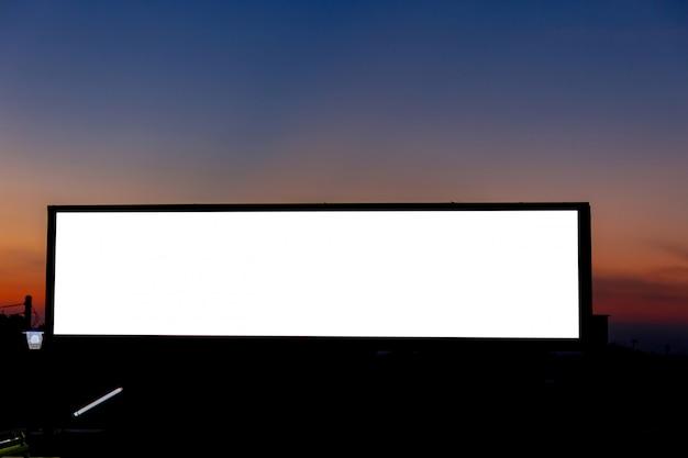 ブランクの看板の白い画面ポスターのモックアップ画像と広告のための朝の空に導かれました。