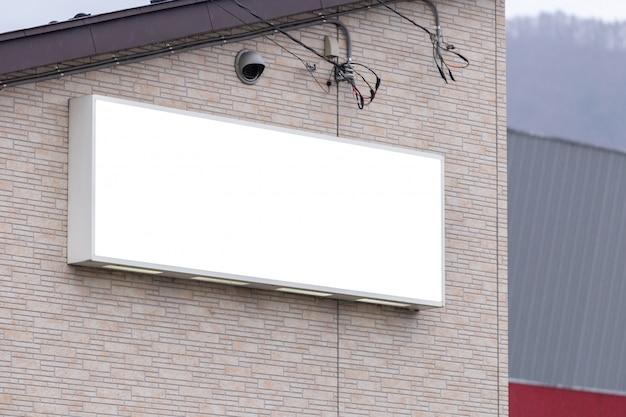 ブランクの看板ホワイトスクリーンポスターのモックアップ画像と広告のための店頭の外側を導いた