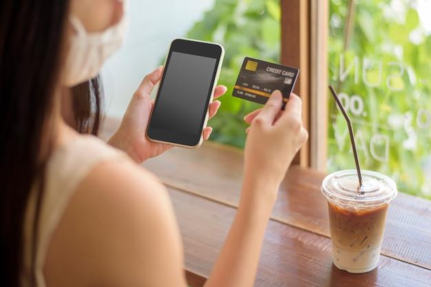 女性の手がクレジットカードで携帯電話のモックアップを持っています。