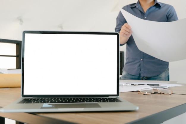 オフィスで図面設計プロジェクトを指すエンジニアとモックアップ画面のラップトップ