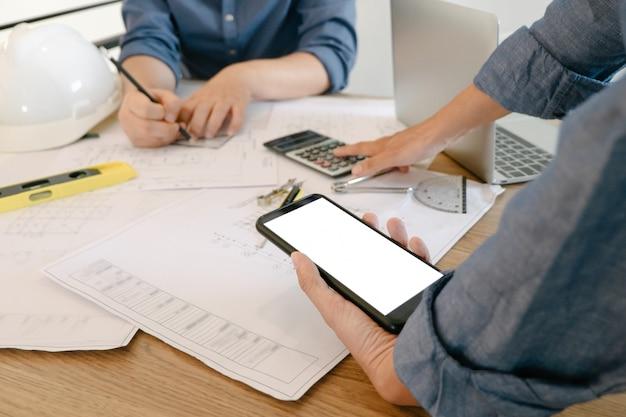 オフィスでプロジェクトに取り組んでいるエンジニアとスマートフォンのモックアップ