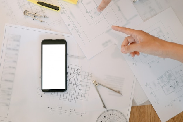 青写真とオフィスの木製テーブルの上の電卓を持つエンジニアツールのモックアップ画像