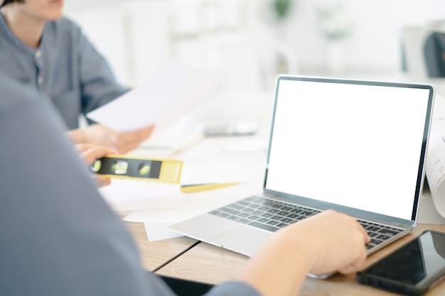 ラップトップを使用してオフィスの設計建築プロジェクトを描くエンジニアのモックアップ画像