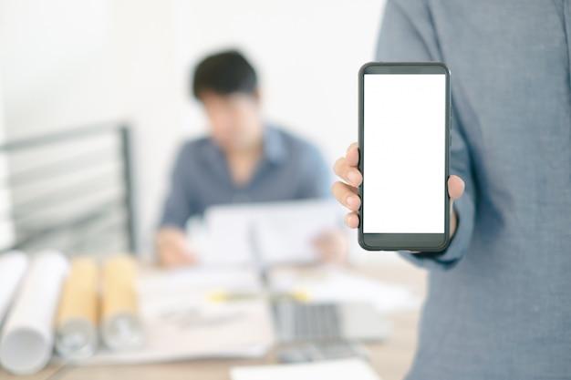 オフィスでのスマートフォンデザインビルディングプロジェクトを示すエンジニアのモックアップ画像