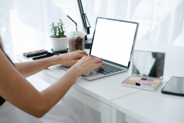 スマートフォンとラップトップでオンラインショッピングサイトで楽しんでいるクレジットカードを保持している美しい女性のモックアップ