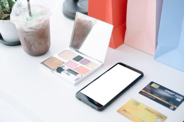 携帯電話とクレジットカードとコーヒーカフェの白いテーブルのモックアップ