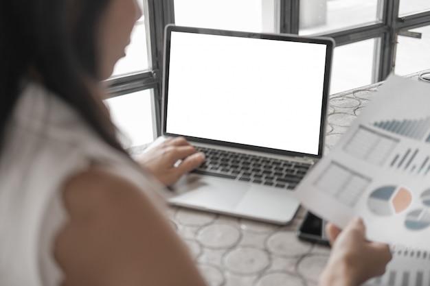 スマートフォンのラップトップとオフィスでドキュメントを扱うビジネス女性を閉じるのモックアップ