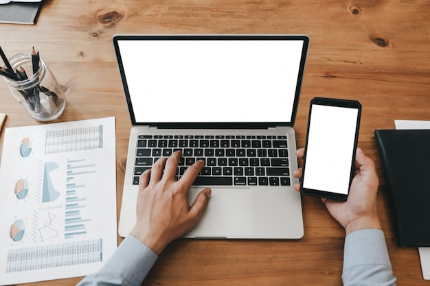 スマートフォンノートパソコンとオフィス、モックアップコンセプトのドキュメントを扱うビジネス女性を間近のモックアップ画像