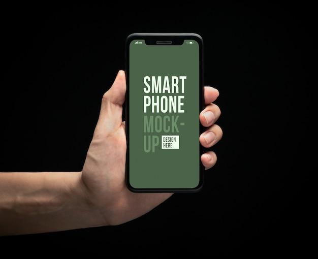 あなたのデザインの画面モックアップテンプレートと現代のスマートフォンを持っている手