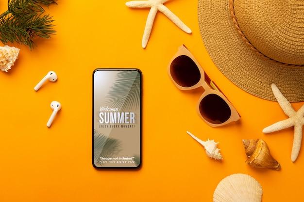 鮮やかなオレンジ色の電話モックアップテンプレートとビーチアクセサリーで夏の背景