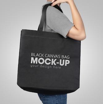 黒のトートバッグを持つ女性モックアップ