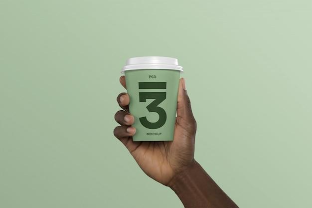 コーヒーカップのモックアップを持っている人