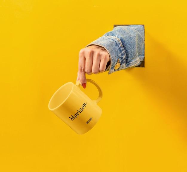 手のモックアップとカップ