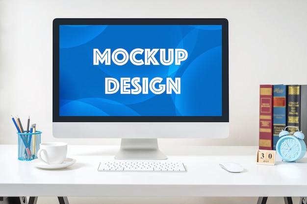オフィスの白い机の上のモックアップのコンピューター表示。