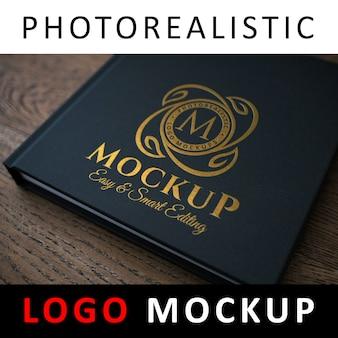 ロゴモックアップ - 黒い本の表紙に金箔のロゴ