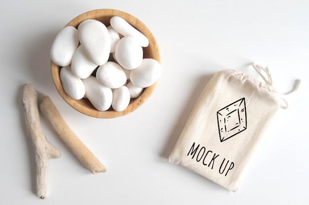 白い小石と白いテーブルに木製の素朴な棒で綿の袋またはポーチとボウルのモックアップします。