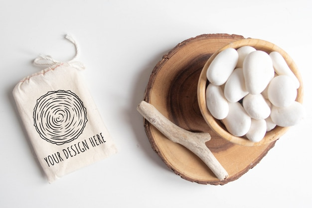 綿の袋またはポーチと白い小石と白いテーブルに木製のカットツリーセクションとボウルのモックアップします。
