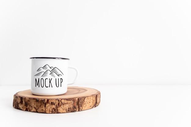 素朴な木製のカットセクションモックアップに白いマグカップ。