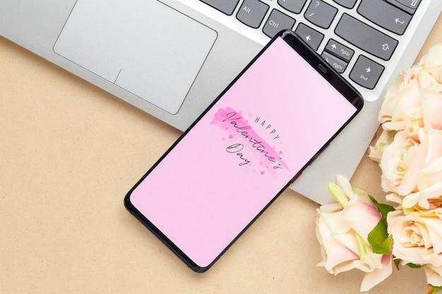 コンピューターのラップトップとバレンタインのバラの花のモックアップスマートフォン