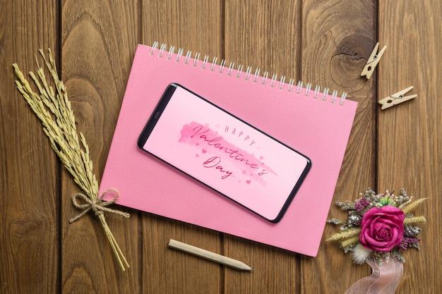 木の上のノートとクラフトのバラの花のモックアップスマートフォン