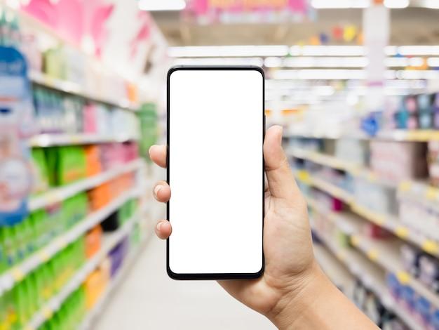 ぼやけているスーパーマーケットと空白の画面を持つモックアップ携帯電話