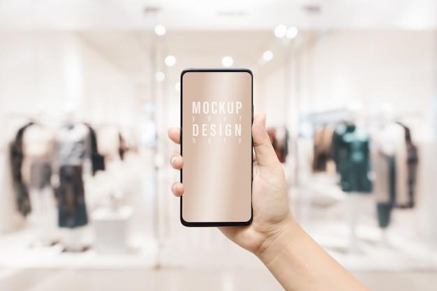 モックアップ白い空白の画面の携帯電話。広告アートワークのぼやけた女性服店背景を持つスマートフォンを持っている手。