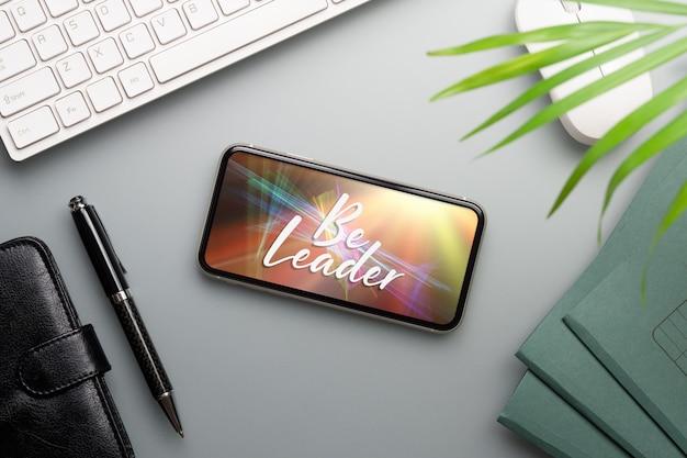 作業オフィスの机の上のモックアップスマートフォン。
