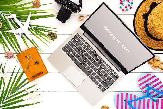 夏休みの白い木製のテーブルの上のノートパソコンのディスプレイをモックアップします。