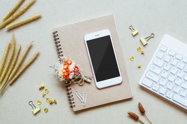 ホームオフィスの机の上の空白の画面携帯電話をモックアップします。