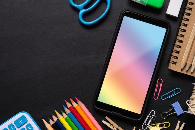 空白の画面の携帯電話をモックアップし、事務用品の背景のミックス