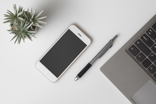 携帯電話のモックアップ、ホワイトオフィスデスクテーブルまたはモックアップ空白画面のスマートフォンとコンピューターのラップトップを持つデスクトップの平面図です。