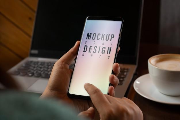 モックアップ画面のスマートフォン。コーヒーショップで現代のスマートフォンを使用して手を閉じる